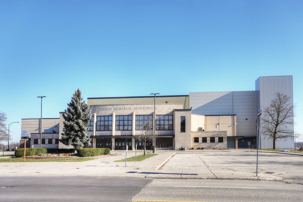 An image of Kitchener Memorial Audiotorium Ontario. It shows a large beige building with a tree in front of it