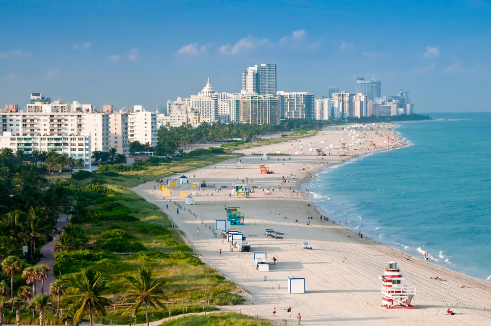 An image of Miami Beach in Florida. It shows a wide beach that curves along the light blue Atlantic ocean. On the left of the frame are dozens of white high rise buildings