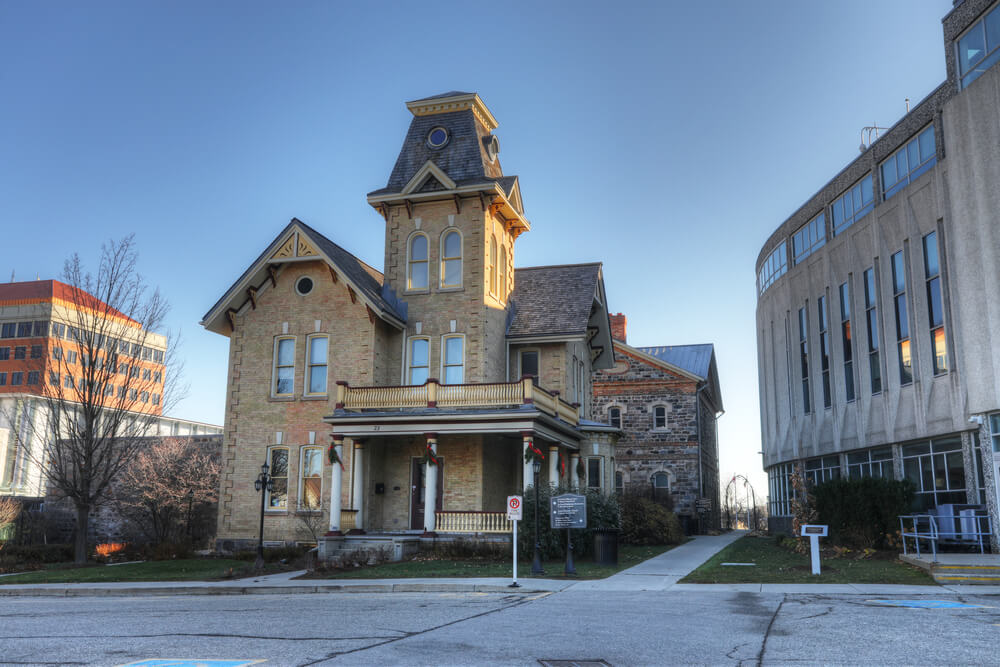 An image of a beautiful old home in Kitchener Ontario. It shows a two storey home made from light brown bricks. It features ornate windows and rails