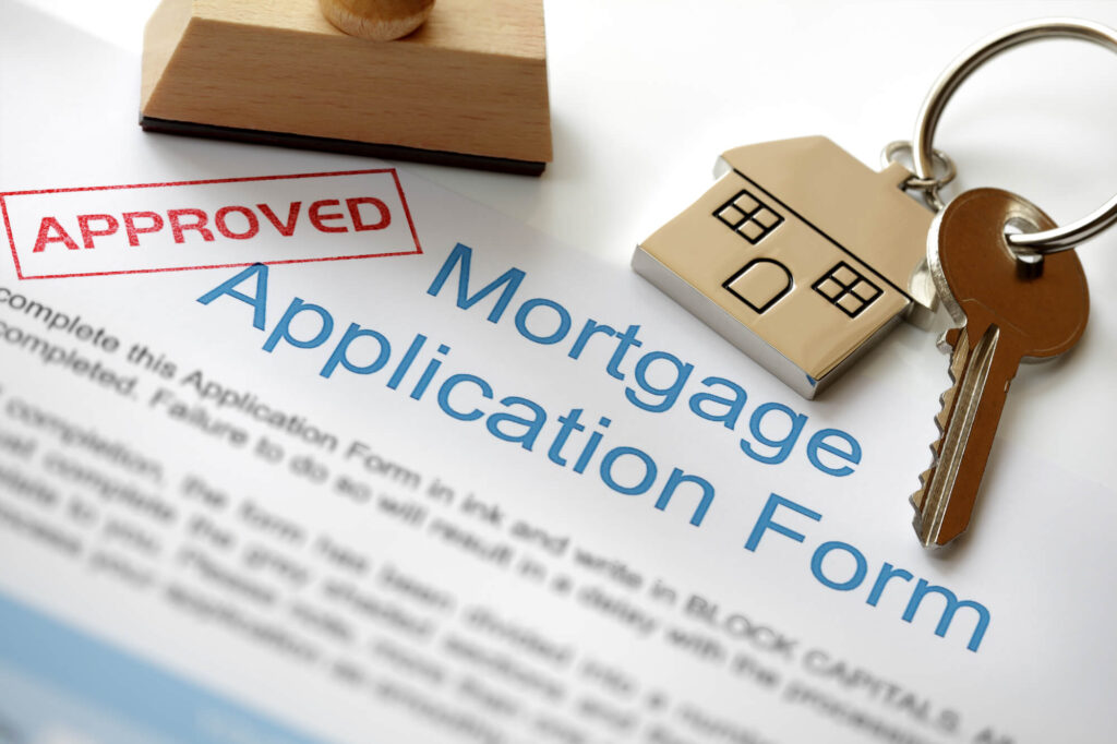 An image of a mortgage application form which is stamped with the word approved. A set of keys and small scullpture of a house sit on top of it