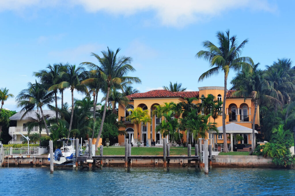 An image showing a luxury waterside home in Florida. The home has dark orange walls and a Mexican influenced design. A boat is docked at a dock in front of the home