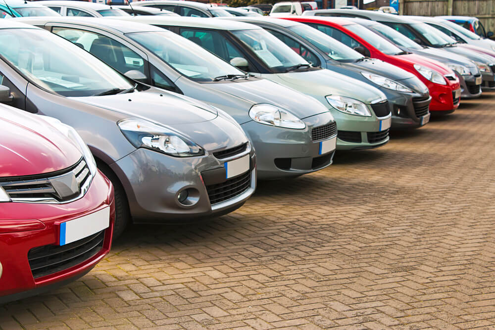 An image showing a second hand car lot in Mexico. It shows a line up of 12 modern cars painted in different colors including red, silver, green, and white