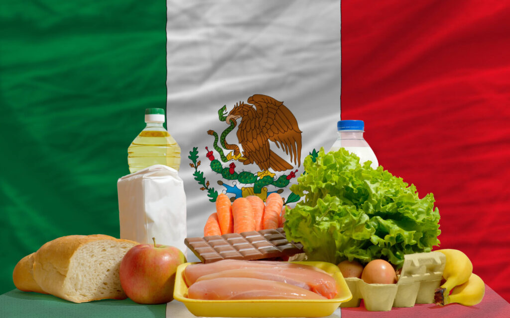 An image showing different foods in front of a Mexican flag. The foods include bread, chicken, milk, chocolate, eggs, and lettuce