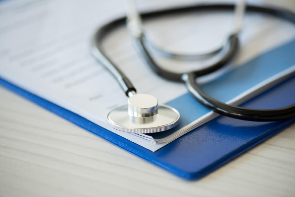 A closeup photo of a stethoscope laying on a clipboard, which represents the cost of healthcare in the 2000s