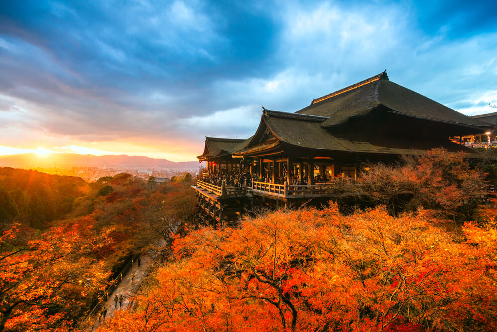 A photo of Kiyomizu-dera Temple in Kyoto, Japan. It shows a large traditional Japanese temple high on a hill lsurrounded by trees. The sun is setting and the sky is bright orange.