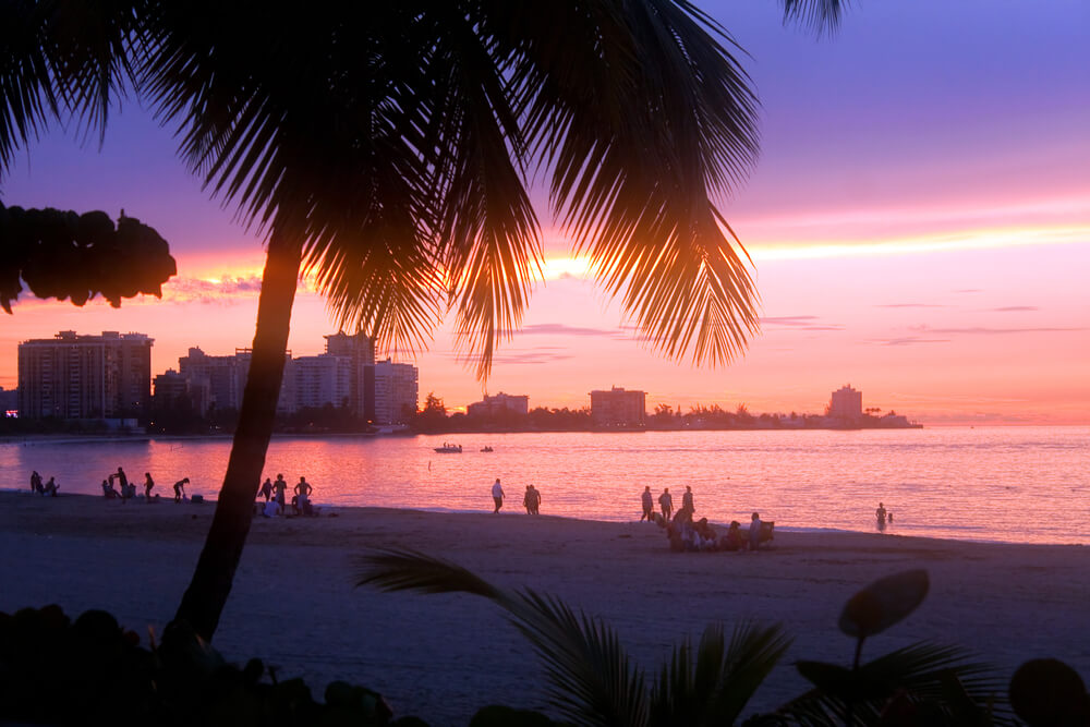 A photo of Luquillo Beach in Puerto Rico during the late afternoon. A beautiful pink sunset is shown