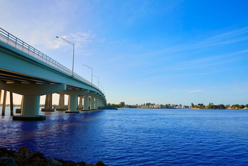 A photo of Marco Island bridge in Florida. It shows a large concrete bridge crossing deep blue water