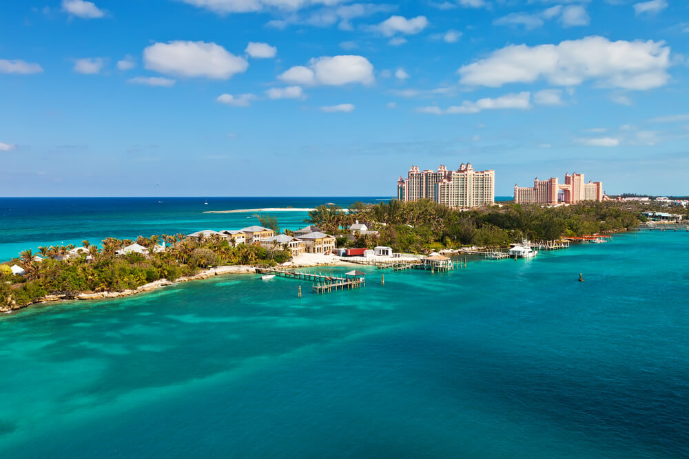 A photo of Nassau, Bahamas. It shows a narrow island with a large hotel that is surrounded by aqua blue water and dozens of boats
