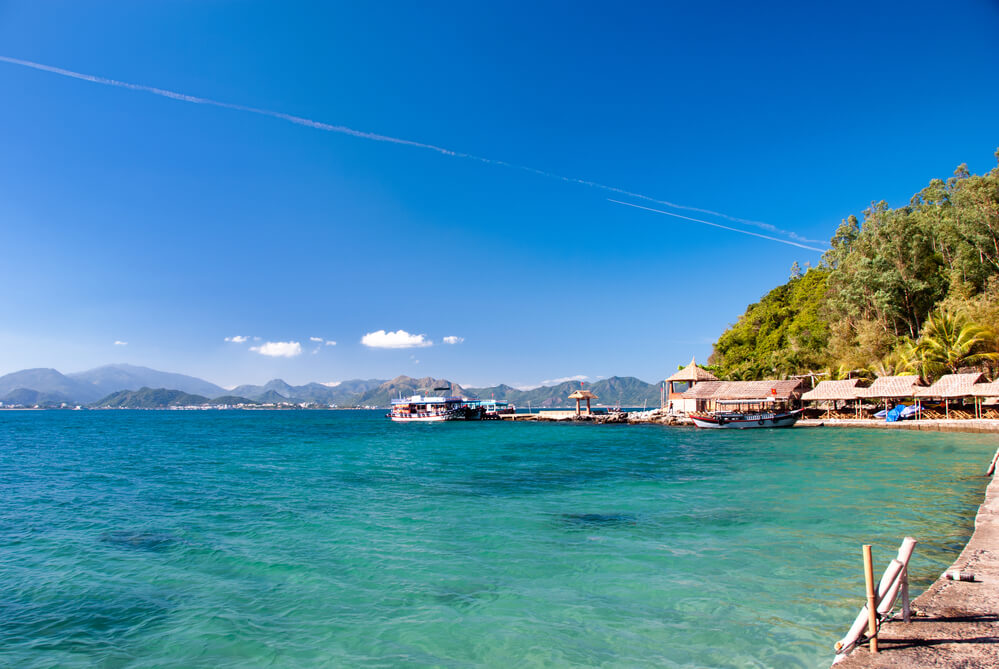 A photo of Nha Trang Beach in Vietnam. It shows a calm aqua blue ocean lapping against the shores of a small jetty. There are several small buildings and a ferry in the distance