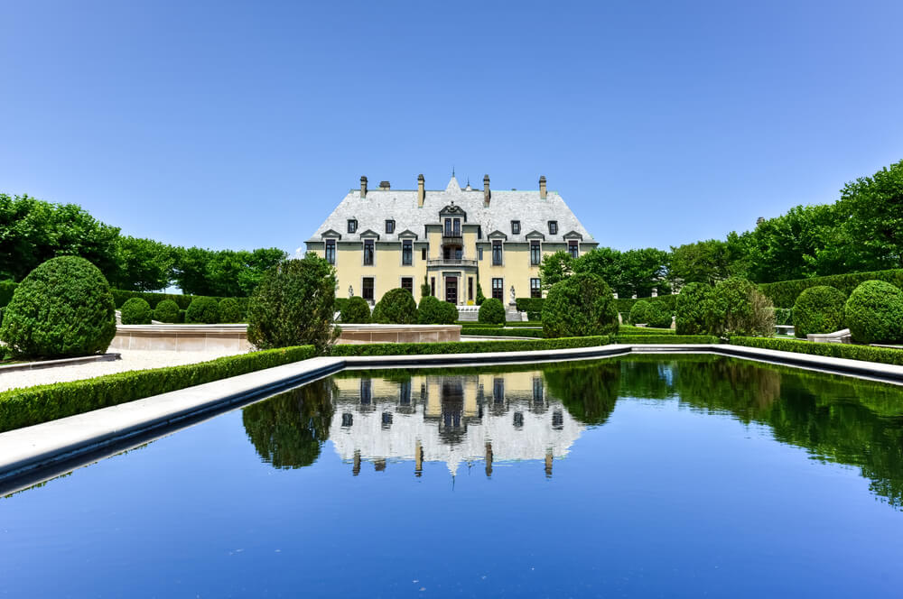A photo of Oheka Castle Grounds near Huntington Long Island. It shows a large creme colored classical mansion behind a large pond