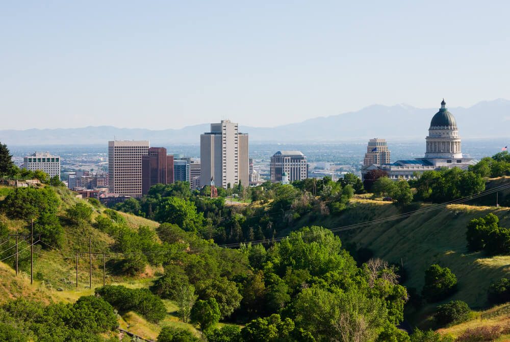 A photo of Salt Lake City in Utah. The photo is taken from the outskirts of the city and shows a sweeping green hilllside leading into the city
