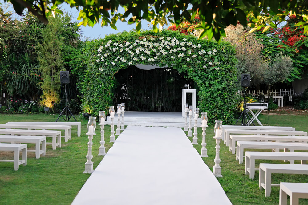 A photo of a beautifully decorated garden set up for a wedding. It includes flowers, seating, and an altar