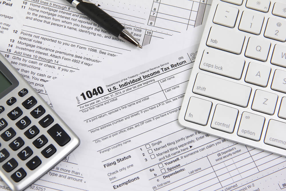 A photo of a calculator, pen, and tax forms including a 1040 individual tax return form