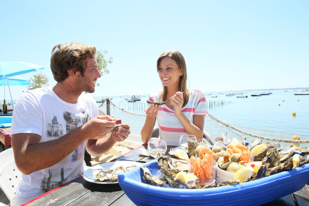 A photo of a couple eating Oysters at a ocean side restaurant