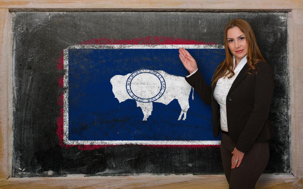 A photo of a female teacher standing in front of a blackboard featuring the Wyoming flag