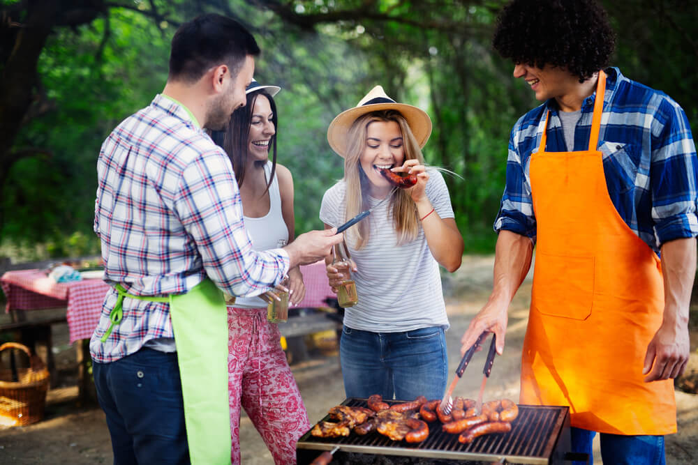 A photo of a group of friends stanig around a BBQ. It shows two men and two women, with one of the men holding a pair of tongs
