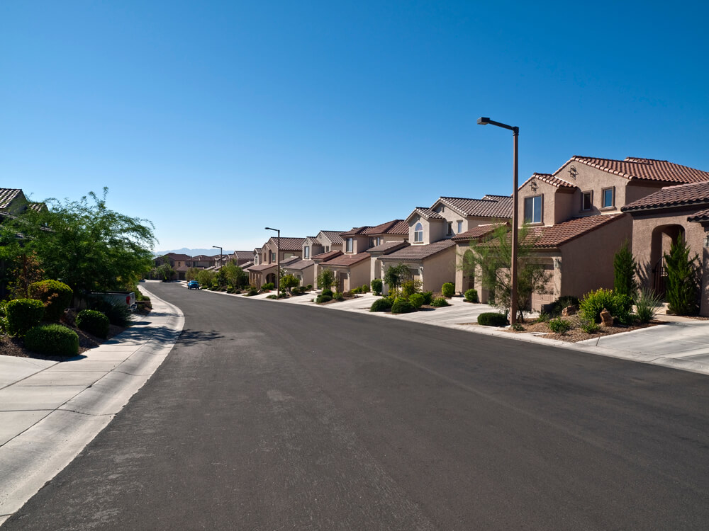A photo of a residential suburb in Nevada, showing dozens of modern houses along a wide street