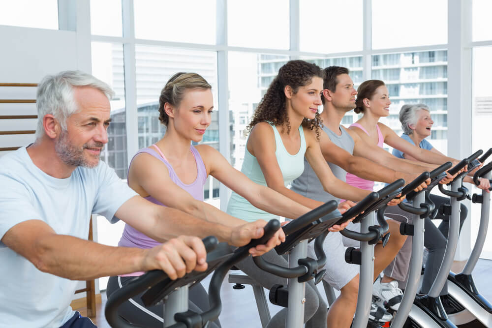 A photo of a spin class with several participants on stationary bikes. The class includes a mix of young people and seniors