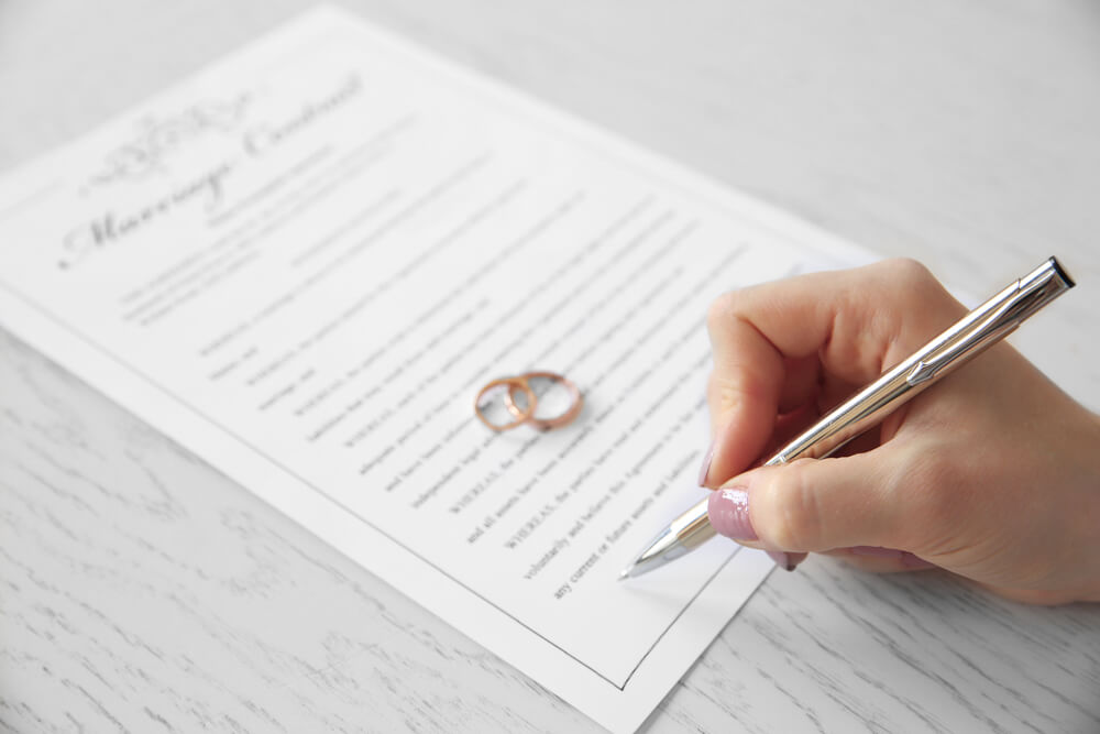 A photo of a woman's hand holding a pen as she signs a marriage contract. There are two rings sitting on the document