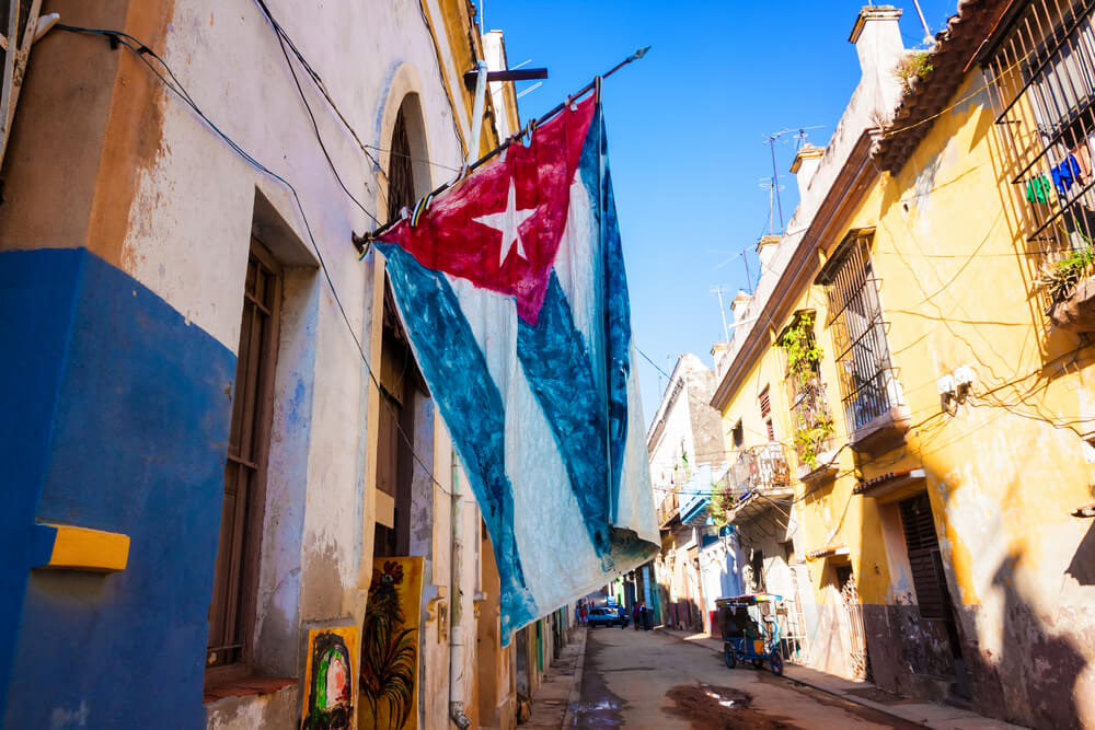 A photo of an old Cuban flag hung from a building in Old Havana, Cuba. It shows a narrow street with old brick buildings