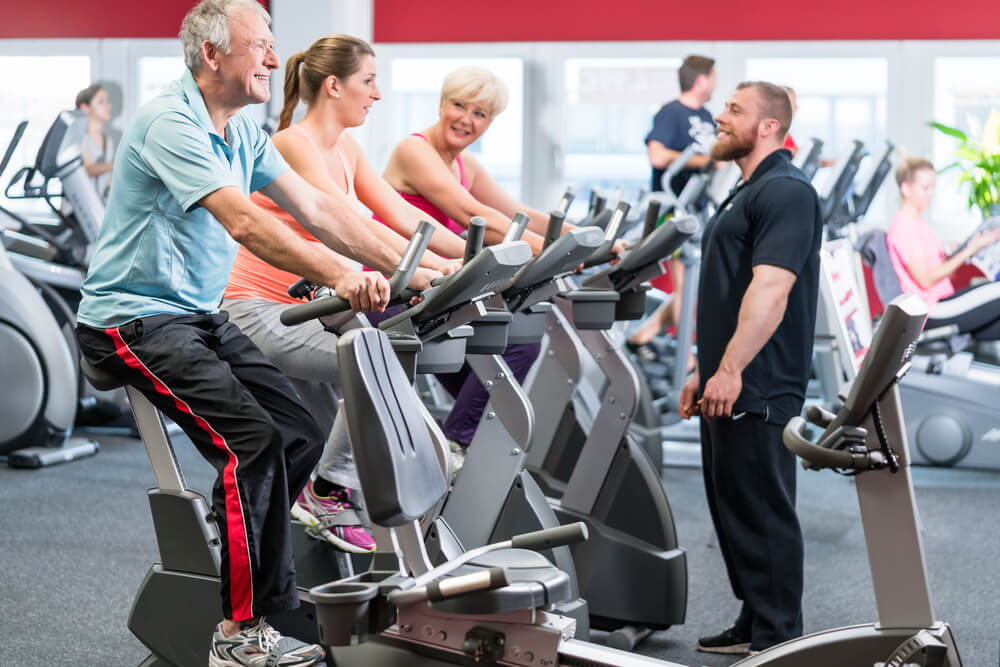 A photo of an older couple and a young woman on stationary bikes at a gym. An instructor is standing in front of the bike riders