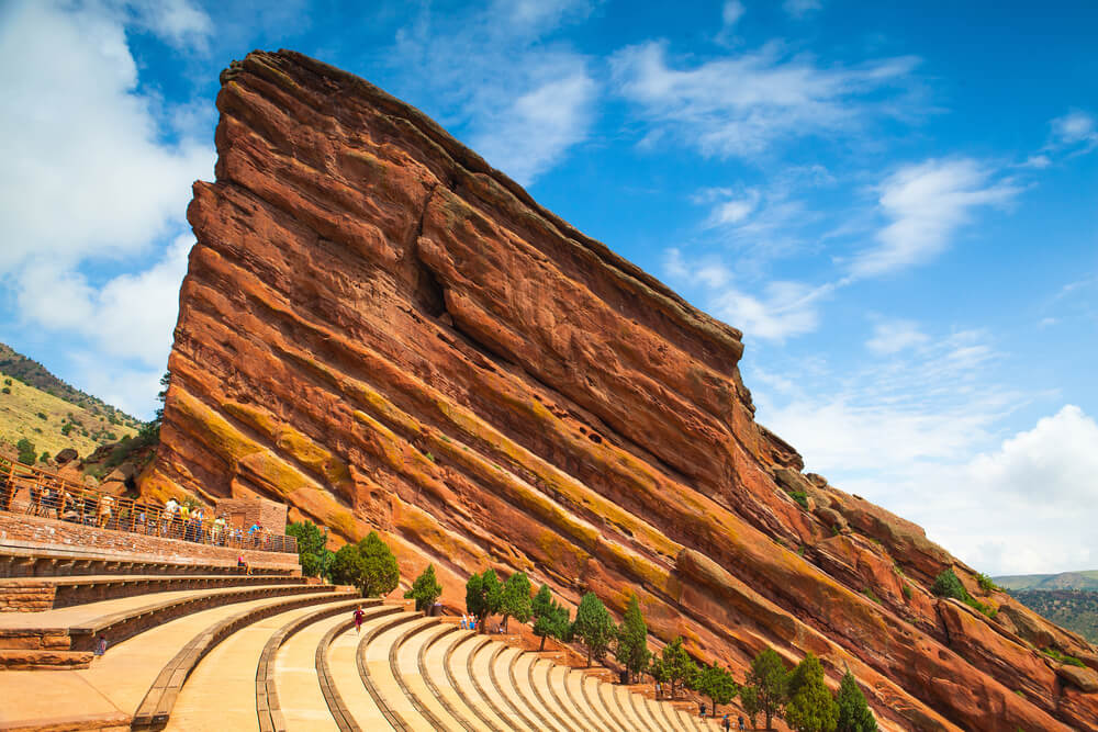 A photo of the Famous Red Rocks Amphitheater in Denver. It shows a series of rock steps carved into a hill with a large red colored rock wall behind it