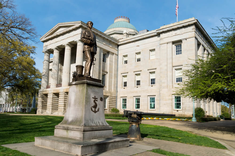 A photo of the North Carolina State Capital Building. It shows a large bronze statue and a 3 story building in a classical architectural style