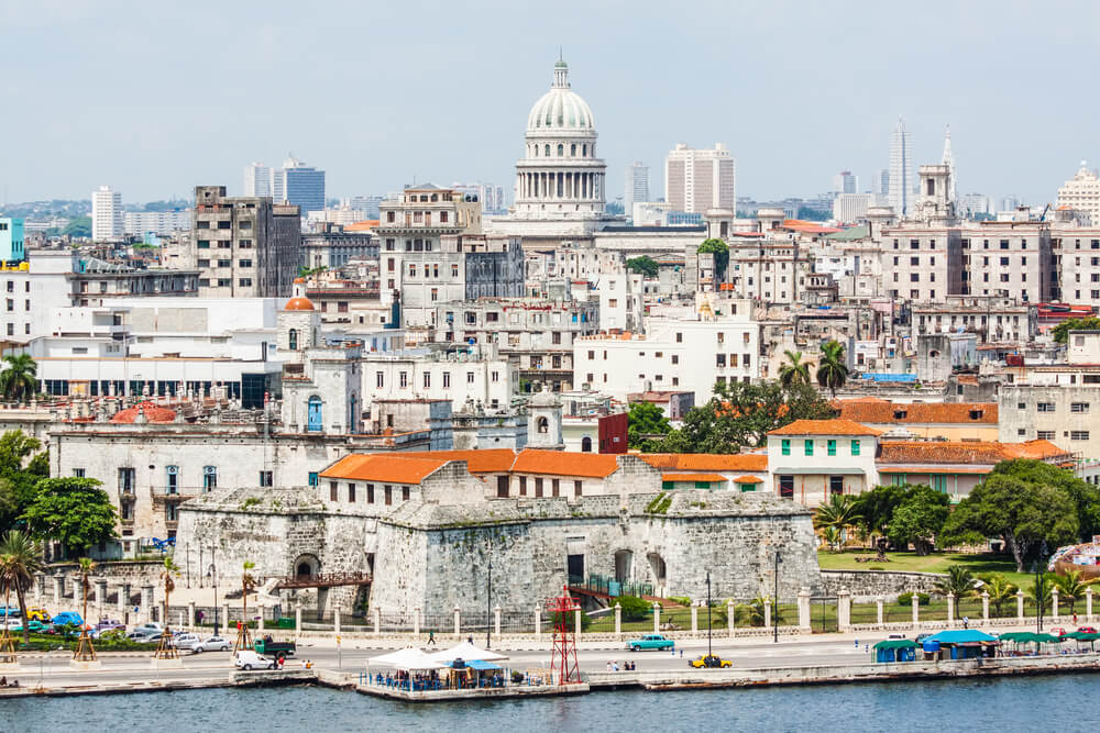 A photo of the city of Havana including several famous buildings. A river is in the foreground of the image and the cityscape shows dozens of beautiful old buildings