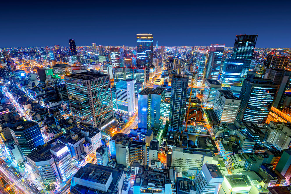 A photo of the cityscape of Osaka taken at night. It shows dozens of large sky scrapers