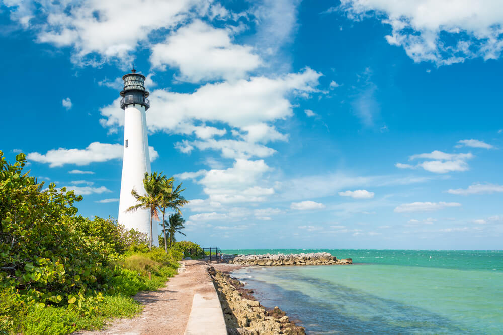 A photo of the famous lighthouse at Key Biscayne, Miami. It shows a white lighthouse on the left of the image, with an aqua colored ocean on the right. There is vegatation surrounding the lighthouse