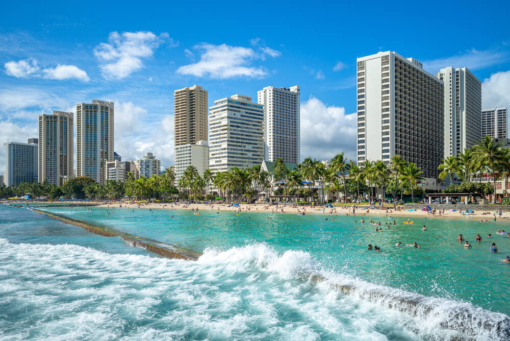 A photo of the skyline of Honolulu at Waikiki beach, Hawaii. It shows a huge beach pool packed with people and several large sky scrapers