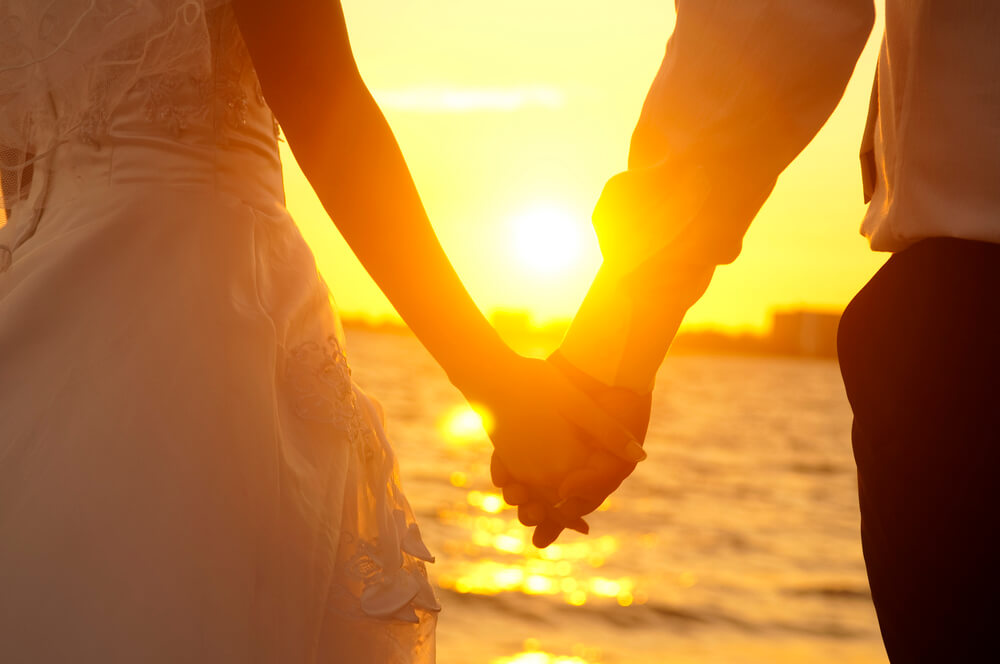 A photo of two people holding hands as they walk along a beach in Cuba. The sun is setting and the sky has a brilliant orange color