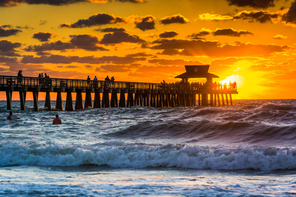 A photo showing a sunset over the fishing pier and Gulf of Mexico in Naples, Florida