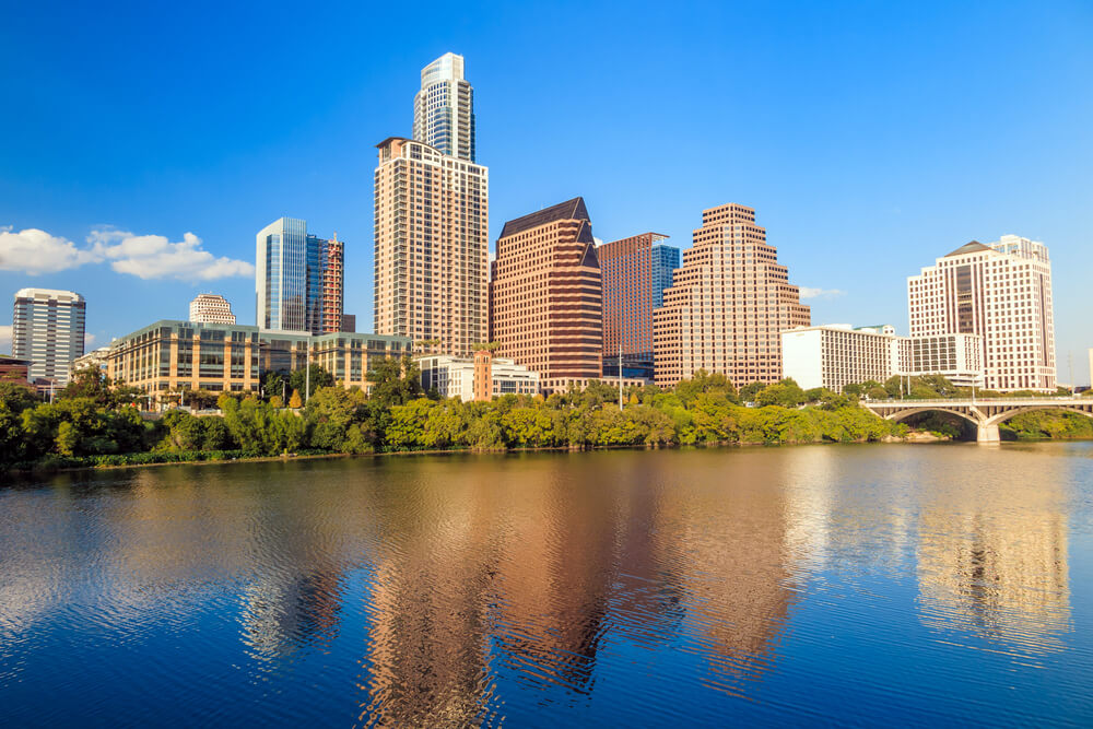 A photograph of Austin Texas shot during the day. The photo includes a large body of water in the foreground ad several skyscrapers in the background
