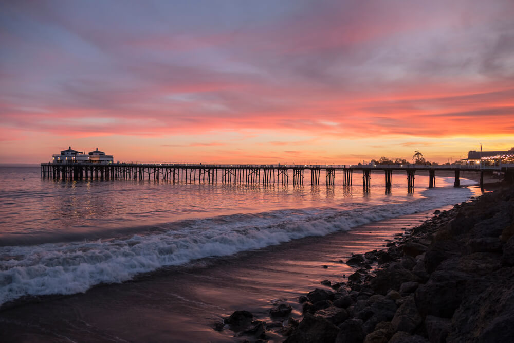 A photograph of Malibu Pier in California during a Sunset. It shows a very long pier on a beach at high ride, with a pink and purple sky
