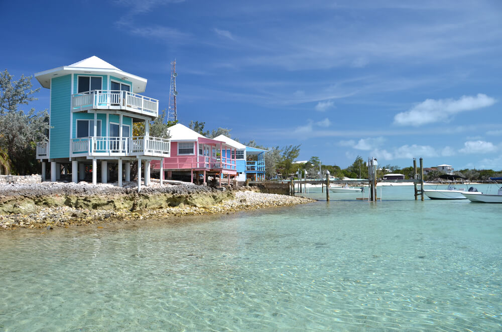 A photograph of Staniel Cay Yacht Club. Exumas, Bahamas. It shows 3 colorful buildings on the shoreline of a beautiful lightly colored ocean
