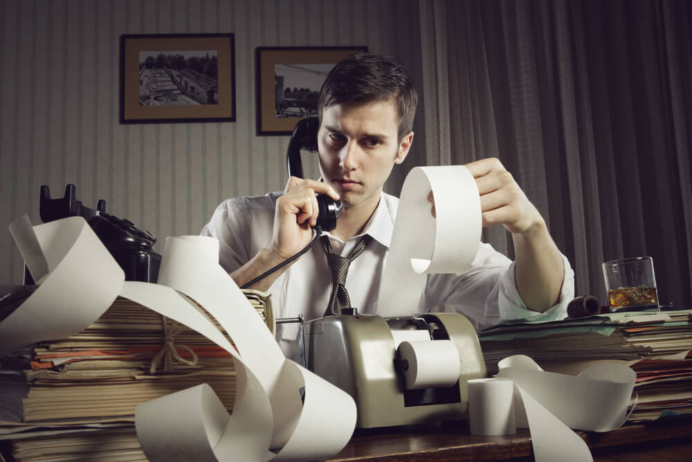 A photograph of a man sitting at a desk on the phone and reading a print out of his taxation bill