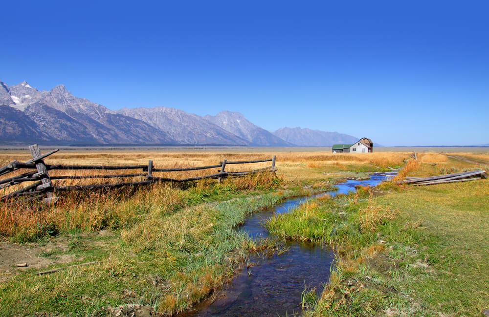 A photograph of an old barn in Grand Tetons in Wyoming USA. It shows a broken down fence, small stream, and arn in the middle of a paddock. To the left of the image is a mountain range