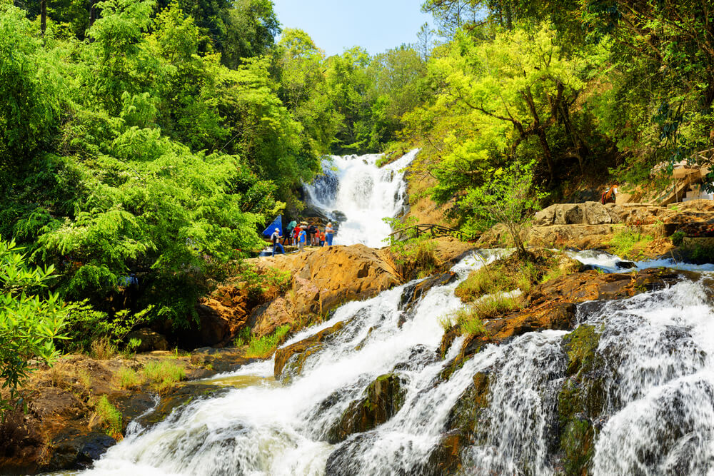 A photograph of several tourists standing on top of Datanla Waterfall located just outside of Da Lat City in Vietnam. It shows a huge waterfall surrounded by lush green vegetation