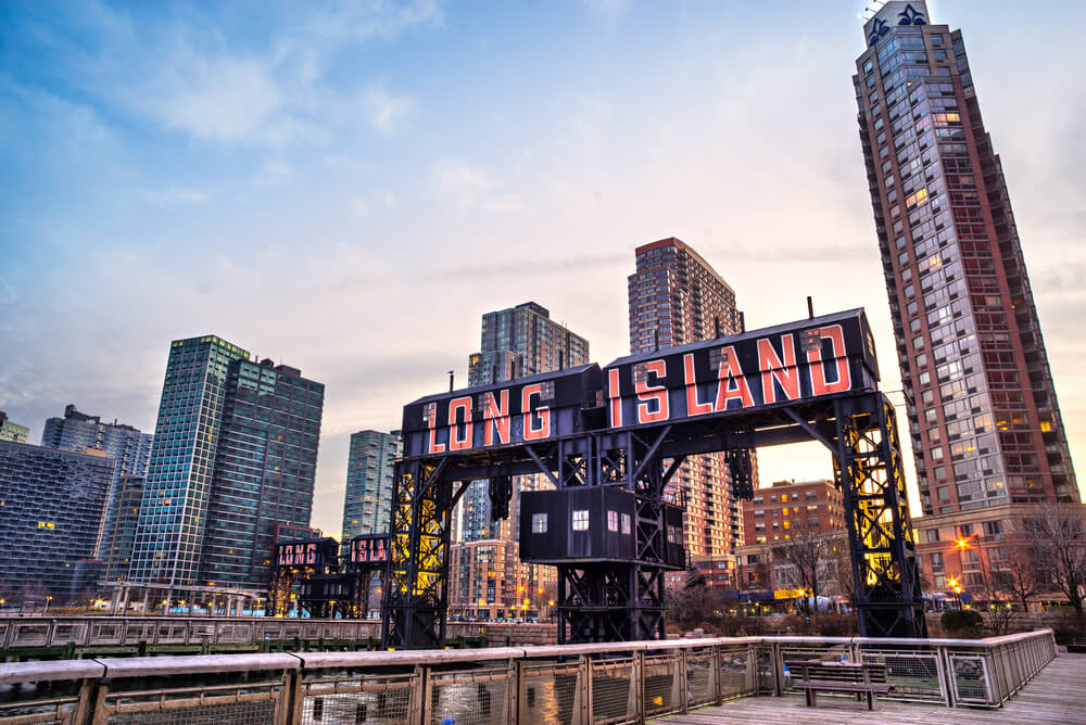 A photograph of the Long Island sign in New York. It shows a huge brightly colored sign for Long Island with several large sky screapers in the background