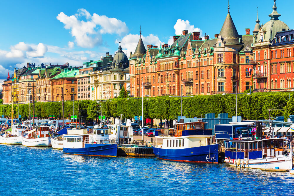 A picture of a city in Sweden showing luxurious apartments by the water. There are dozens of boats in the water. This photo shows how expensive Sweden is