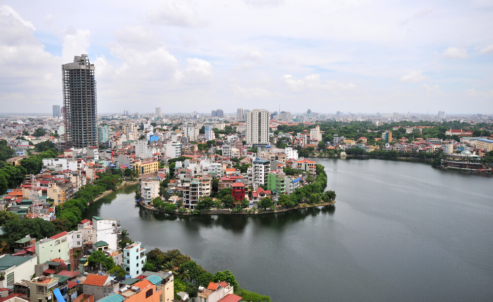 A shot of the Hanoi, Vietnam cityscape. It shows dozens of mid level buildings on outcroppings of land that are surrounded by a large river