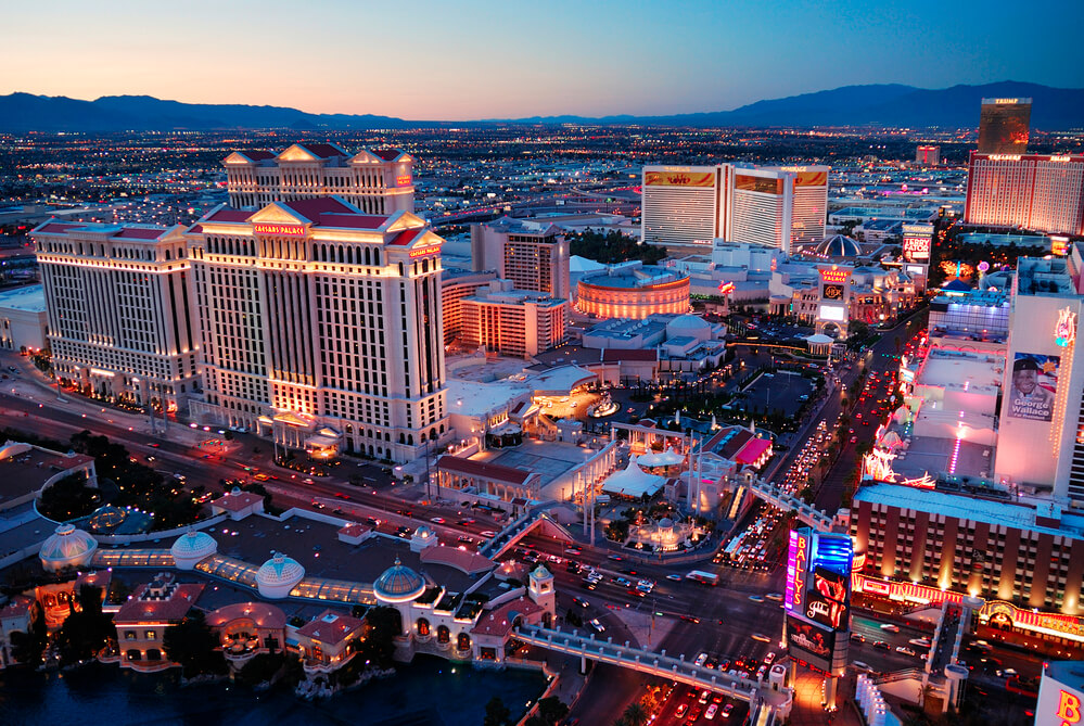 An aerial photograph of Las Vegas at night with dozens of high rise hotels and casinos on display. It shows how successful the Nevada economy is