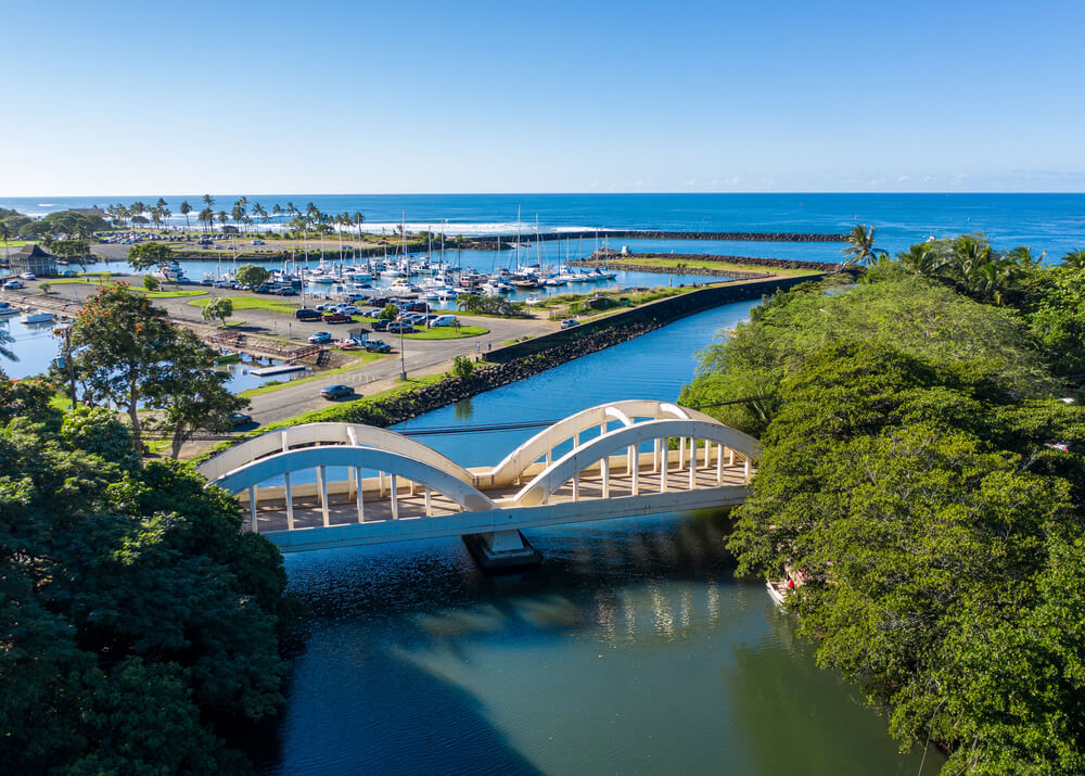 An aerial picture of a twin arched bridge over the river Anahulu in Haleiwa on Oahu. It shows a large bridge over a caal which leads towards the ocean