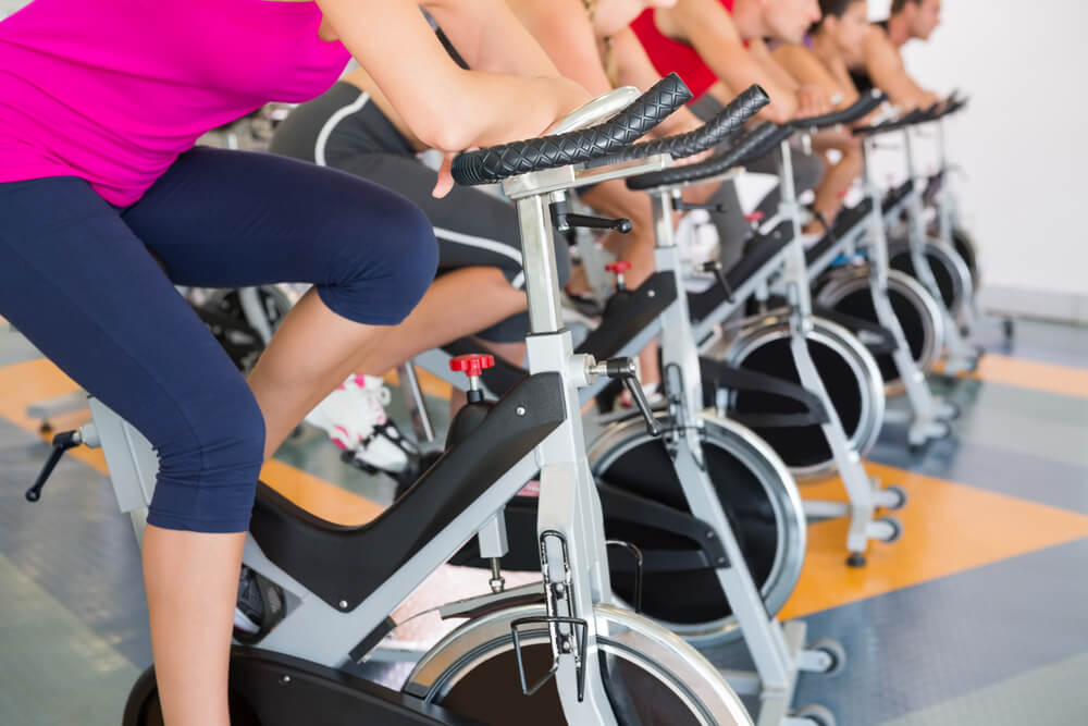 An image of a spin class. It shows the bottom legs of several people sitting on stationary bicycles