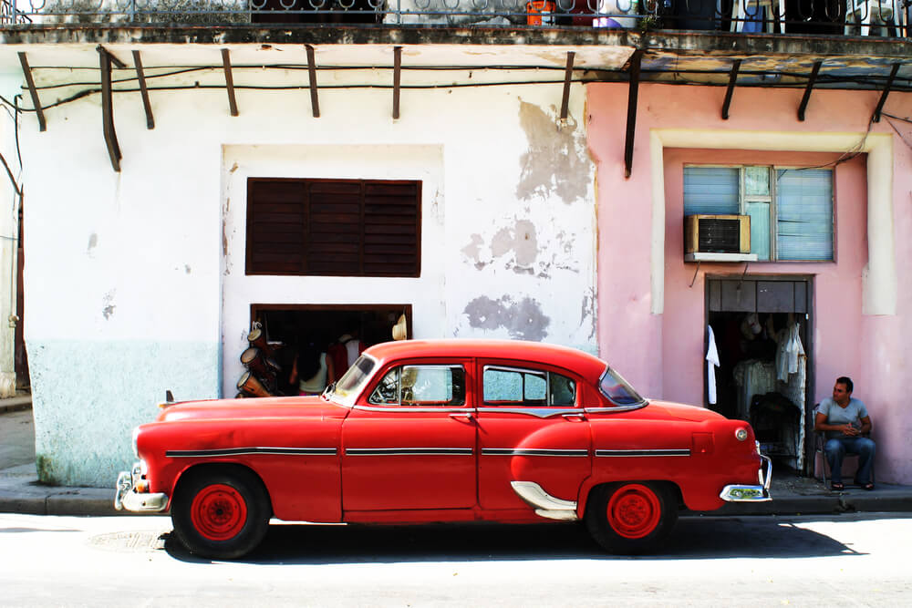 An image of an old 1960s car in front of a run down building in Cuba. It represents the fact that many buildings in Cuba are in bad shape