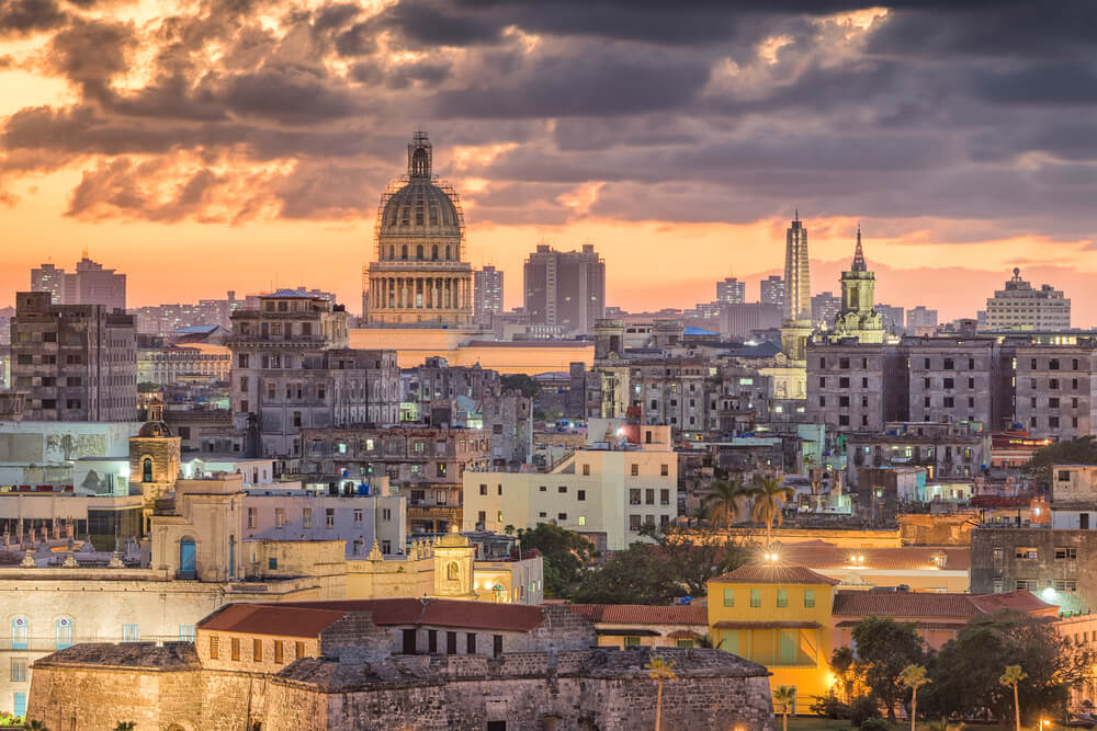 An image of the Havana skyline at night. It shows a vibrant city with a classical architectural style