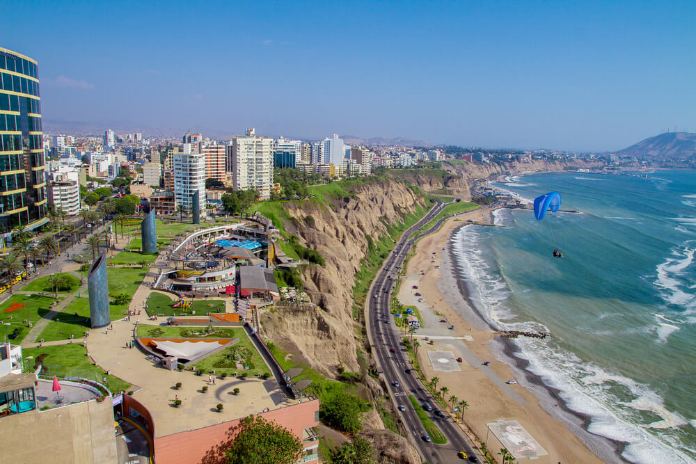 A photo of Lima, Peru. It shows several modern buildings on a hill overlooking a two lane highway and beach. The sky is bright blue