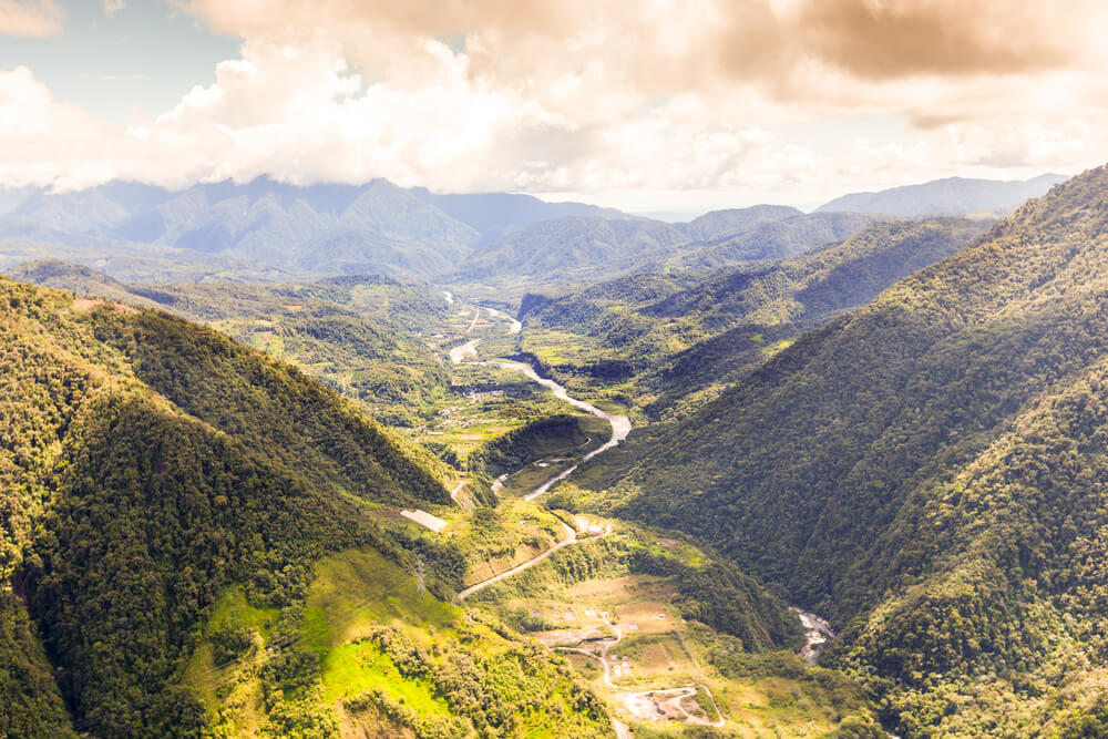 A photo of Pastaza River In The Andes Ecuador. It shows a vast tree lined valley with a river in its center