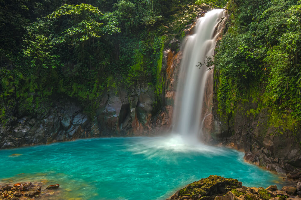 A photo of Rio Celeste Waterfall in Costa Rica. It shows a small waterfall pouring into a light blue water hole, surrounded by lush vegetation